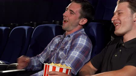зрителей : Sliding shot of two young cheerful male friends eating popcorn, laughing joyfully while watching a movie at the local cinema. Young people relaxing at the movie theatre. Food, leisure concept.