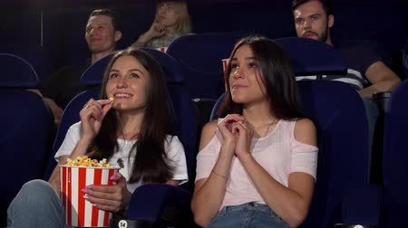 зрителей : Happy female friends eating popcorn, while watching a movie together at the cinema. People enjoying new film premiere at the movie theatre. Friendship, entertainment, leisure concept.
