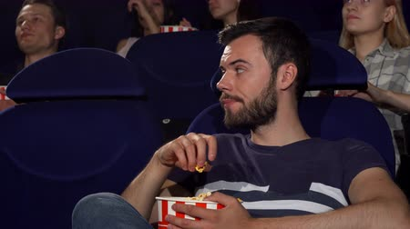 aborrecido : Attractive young man looking bored while watching a movie at the cinema. Handsome man eating popcorn, looking annoyed sitting at the cinema auditorium. Emotions, expressive concept.