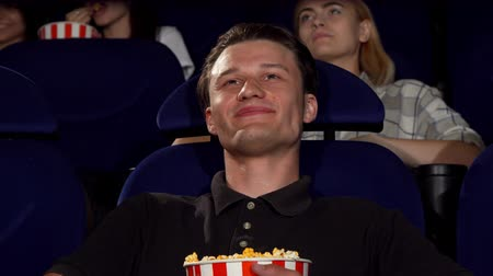 премьера : Cropped shot of a handsome young man enjoying movies at the cinema, eating popcorn, smiling to the camera. Attractive cheerful man watching film premiere at the movie theatre.