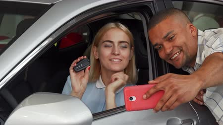 araba : Beautiful young happy woman sitting in an auto holding car keys while her boyfriend using smart phone, taking selfies. Cheerful couple celebrating buying new automobile. Transport concept. Stok Video