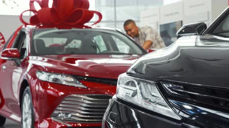 prawo jazdy : Selective focus on a car on the foreground, male customer checking out an auto on the background. Man choosing new car to buy, looking inside the vehicle. Driving, lifestyle, safety concept.