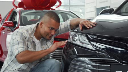prawo jazdy : Young handsome African man smiling to the camera showing thumbs up, while examining an automobile for sale at the local dealership. Male customer choosing new auto to buy. Driving concept.