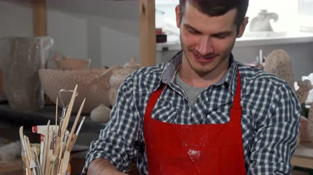 kitchenware : Sliding shot of a young handsome male potter smiling joyfully to the camera, while working with clay, shaping a bowl form. Professional pottery artist making ceramic kitchenware. Stock Footage