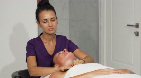 ayurveda : Female therapist doing soothing relaxing neck massage for her client. Professional masseuse giving neck and shoulders massage to a mature female. Relaxation, recreation, service concept.