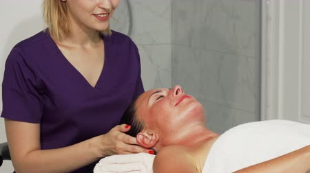 ayurveda : Cropped shot of a professional therapist smiling while massaging head of her female client. Mature woman smiling with her eyes closed while relaxing at massage center. Service, hotel concept. Stock Footage