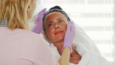 descamação : Beautiful mature woman getting her skin examined by professional dermatologist. Cosmetologist examining face of her female client before providing treatment. Dermatology, skincare concept.