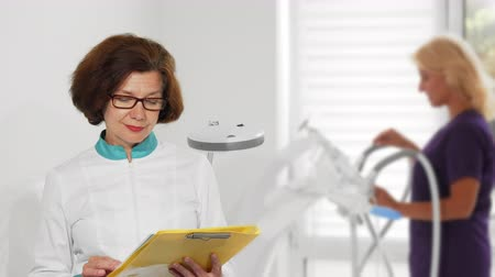 professionalism : Cheerful female senior practitioner smiling to the camera showing thumbs up, while working at the hospital. Elderly female doctor posing proudly at her clinic. Medicine, healthcare, job concept. Stock Footage