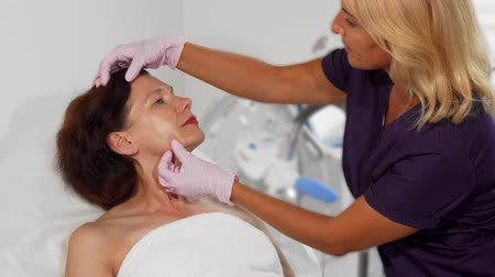 megbeszélés : Cropped shot of a senior woman preparing to get facial treatment at the beauty clinic, getting her skin examined by cosmetologist. Professional dermatologist checking face skin of female patient.