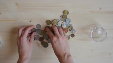 stash : Woman pour out coins from jar to wooden table and select some coins