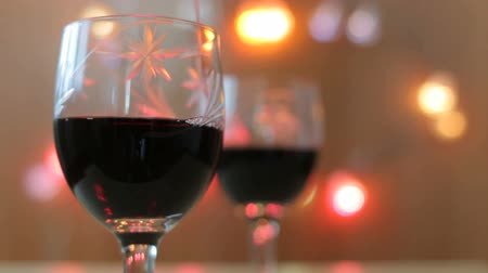 цвет бордо : Pouring red wine into glass. Two glasses, lights Стоковые видеозаписи