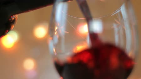 цвет бордо : Pouring red wine into a glass close up. Lights background