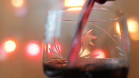 цвет бордо : Close up pouring red wine into a glass. Lights background