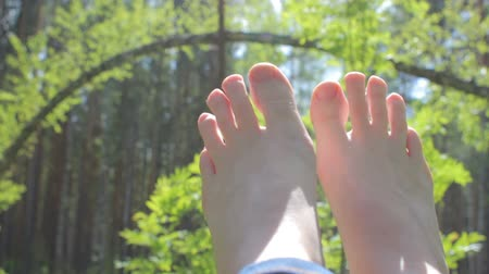 dangle : Barefoot woman relaxing on nature, enjoing sun and summer, women feet