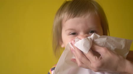 alergia : Mothers hand helping little girl to blow nose by napkin indoor. Woman keeping napkin near her daughter face while toddler blowing her nose. Adult helps baby and taking care of infant during sickness