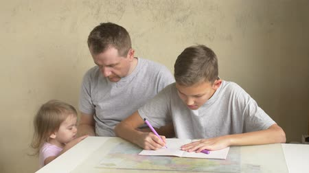 отцовство : Two siblings claim fathers attention - son doing homework, small daughter showing book with pictures. Paternity leave with children. Man helping boy with writing exercise while girl wishing to play