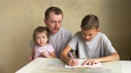 apaság : Two siblings claim fathers attention - son doing homework, small daughter showing book with pictures. Paternity leave with children. Man helping boy with writing exercise while girl wishing to play