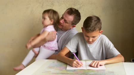 перегружены : Paternity leave - father helping son with homework while daughter trying to escape from his hands. Parent and two children sitting at desk in home together. Overwhelmed man taking care of boy and girl