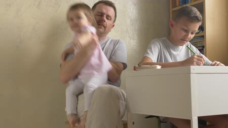отцовство : Small daughter coming to father, son doing homework. Two siblings claim fathers attention at home. Paternity leave with two children. Man helping boy with writing exercise, girl siting in his lap
