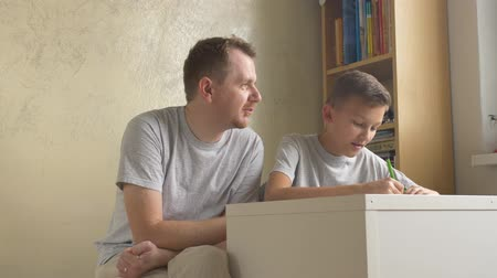 apaság : Father and son - parent giving advice to child at desk in room. Man helping boy with homework at home. Preteen learning under adults control. Teenager speak and write to dads dictation. Two shots