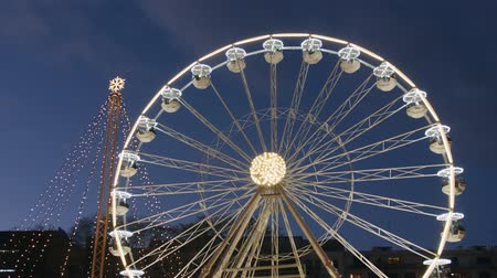 gözlem : Slow spinning twirly ferris wheel and Christmas tree in lights on street fair in evening, dark blue sky. Carnival ride on observation wheel at evening New Year sales. Amusement ride on panoramic wheel