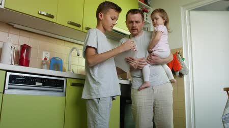 apaság : Fathers day. Cooking father holding small daughter in arms helps son with lessons. Dad making a meal, taking care of small girl and criticizes learning elder boy. 2 children claim parents attention