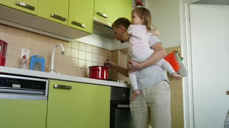 apaság : Fathers day. Cooking father holding small daughter in arms lauds son for homework in kitchen. Dad making a meal, taking care of small girl and praising elder boy for lessons. 2 children and parent