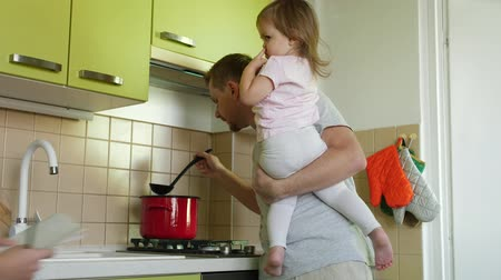 apaság : Fathers day. Cooking father with small daughter in hands lauds son for writing in kitchen. Super dad making a meal, taking care of small girl and praising boy for work sheet. Parent with two children