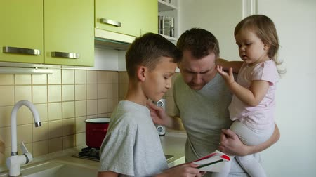 apaság : Fathers day. Cooking father with small daughter in hands commenting sons writing in kitchen. Super dad making a meal, correcting boys work sheet and stopping picking girls nose. Parent take care of 2 children Stock mozgókép