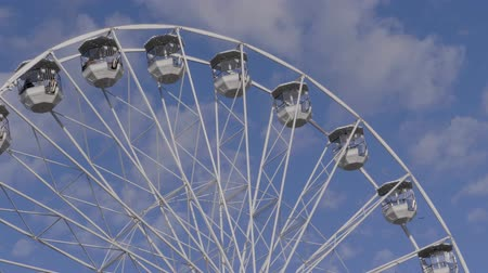 gözlem : Ferris wheel spinning on street fair over blue sky with white clouds, flying birds. Observation wheel with unrecognizable people at sunny day. Underside view of amusement ride. Panoramic wheel, winter Stok Video