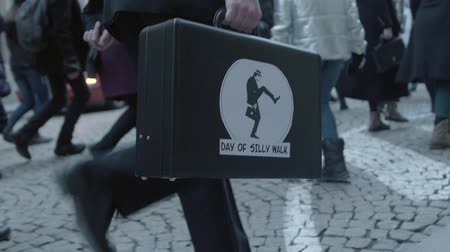 škádlení : Brno, Czech Republic – 01072019: International Day of Silly Walk. Words on attache case during banter march. Suit-case on funny procession of people having fun with up-and-down gait. Citizens feet