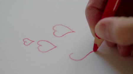 słoneczko : Right hand drawing red hearts by pencil for sweetheart at Valentines day. Preparing Valentine gift for adored person. Happy Valentines day. Outlining hearts contours in love message for darling