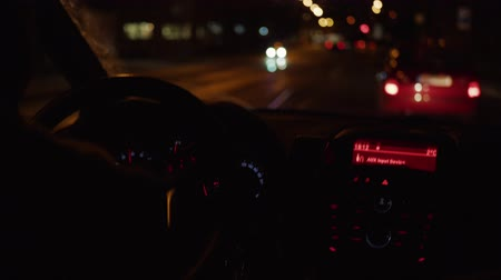 bitola : Man and steering wheel with hands on it during car driving on dark night road. Transport drive on highway. Focus on wheel, sitter view inside of car. Active unfocused transportation in front window