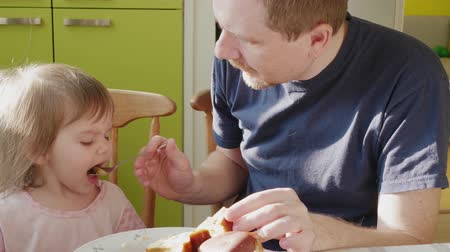 apaság : Father feeding little daughter attracting attention to food in spoon with puree sitting at home. Man taking care of small girl and giving her breakfast at morning. Parent and child eating in kitchen Stock mozgókép