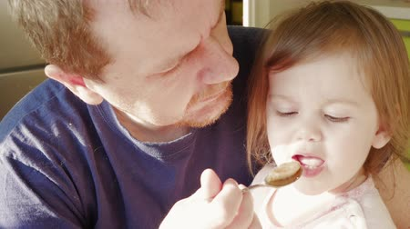 отцовство : Worried and scowling man feeding fidgeting small girl by spoon with puree sitting at home. Father taking care of little daughter and giving her food in morning sun light. Parent and child in kitchen Стоковые видеозаписи