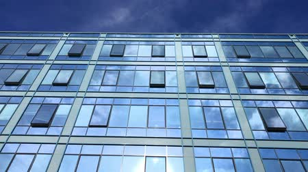 odráží : Blue sky and white clouds reflecting in business building windows. Modern architecture in fine weather. Tinted windows in city on sun light. Office building windows at bright day. Reflection pattern