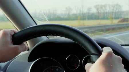 поколение : Hands on steering wheel and car dashboard during day driving out of town. Road in countryside near green fields. Unfocused transport drive on highway meet halfway in front window. Wheel, control panel