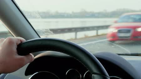 desfocado : Hands on steering wheel and car dashboard during day driving on bridge cross lake. Road near river water. Unfocused transport drive on highway meet halfway in front window. Focus on wheel, dashboard
