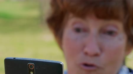 hírnök : Close-up of senior woman talking via mobile video, emotions, focus on mobile. Grandmother chatting via smartphone outdoor. Modern lifestyle of older people on retirement. Active elder lady using phone