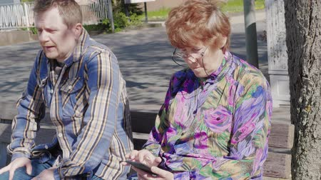 prohlížení : Neighbours on bench with mobile phones outdoor, emotions, day. Man looking at senior woman disapprovingly, sitting down next to her with cellphone. People communication, internet addiction. Adults
