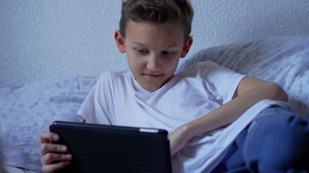 obsession : Teenager boy talking by video call messenger on tablet at home, smiling. Screenager child recording stories, touching screen. Teen chatting via social network on pad at bedroom. Kid using internet