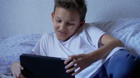 hírnök : Teenager boy streaming live video, calling via call messenger on tablet at home. Screenager child talking, recording stories. Teen chatting via social network on pad, smiling. Kid using internet, talk