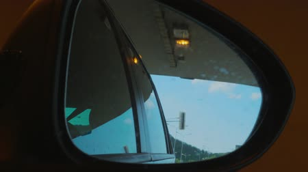 hátsó megvilágítású : Right side rear view mirror of car driving from day light to dark tunnel. Automobile mirror reflecting blue sky, clouds and lamp posts, tunnel lights in dusk on highway. Reflection. Sitter perspective