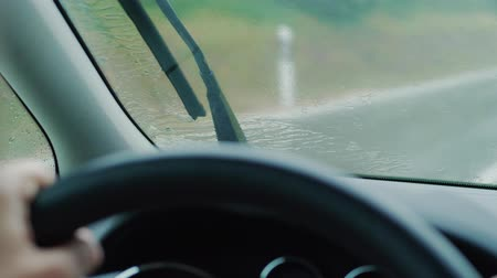 ユニット : Front screen with rain drops on driving car at rainy day, blurred outlines of traffic meeting on wet road in window, cleaning unit. Focus on glass and scatter of rain, sitter view inside of automobile 動画素材