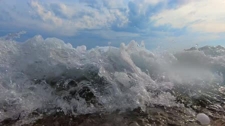 входящий : Oncoming sea wave with seafoam washing-down coast under blue cloudy sky, underwater splash of ground swell. Collapse of incoming waves washing stone shore. Ground sea waves breaking against rocks