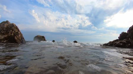 входящий : Oncoming sea wave with seafoam washing-down rocky coast under blue sky with clouds, underwater splashes of ground swell. Ground sea waves breaking against rocks. Air bubbles under water. Curling over