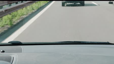 Car driving following at discreet distance in traffic on highway, vehicular distance on road, sitter view, dirty windshield. Blurred outlines of automobile in front screen during drive. Safety concept