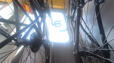 Two bikes hanging on rack in moving train, trees, bright light in window, handheld shot, closeup. Transport bicycle inside of wagon. Transportation of cycle in rail stand. Outside activities concept Стоковые видеозаписи