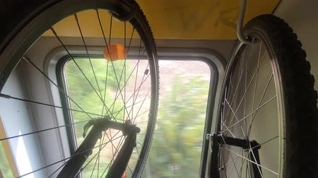 Two bicycles hang on rack in moving train, green trees, bright light in window, handheld. Transport bike inside of wagon. Cycle transportation in rail stand. Outside activities, leisure sport concepts