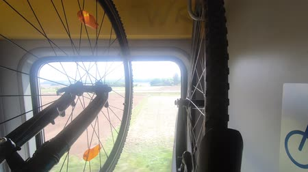 Two bicycles hang on rack in moving train, bike sign on wall, green, field landscape in window, handheld. Transport bike inside wagon. Cycle in rail stand. Outside activities, leisure sport concepts